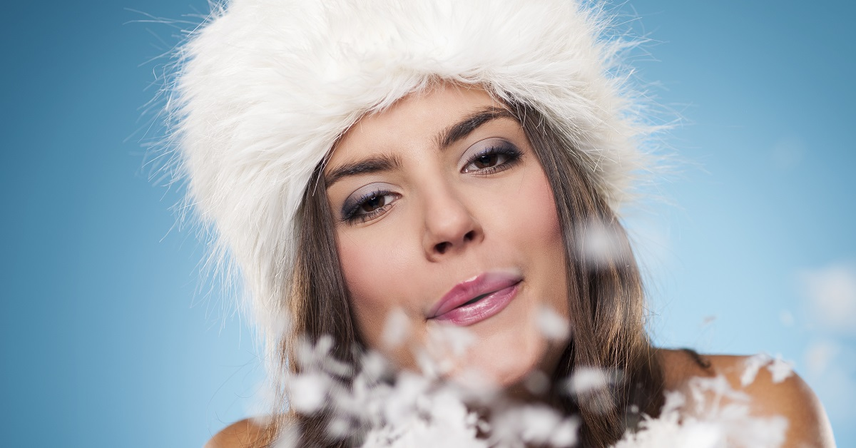 Closeup photo of brunette-haired woman in white, fur winter hat
