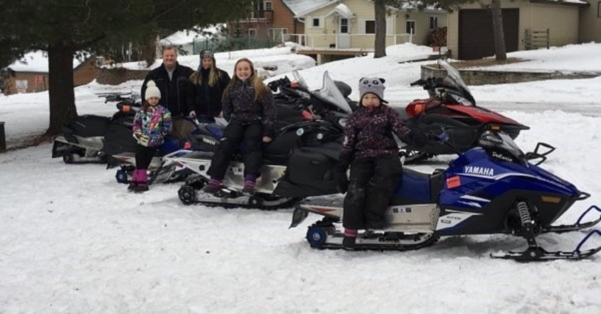 Schuh family members pose outside in the snow with their snowmobiles.