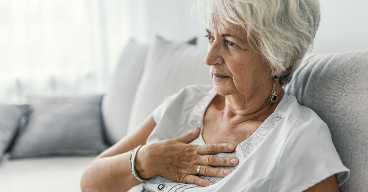 Mature woman with hand held on heart-side of chest