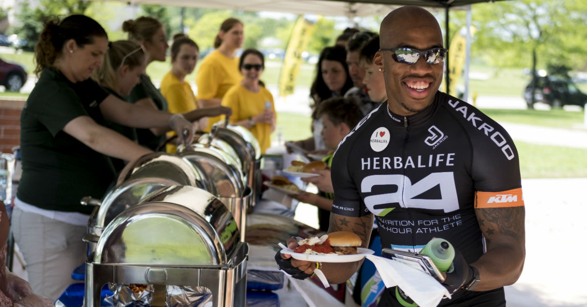 A bike rider carries a plate of food after finishing the BayCare Clinic Century Bayshore to Lakeshore tour.