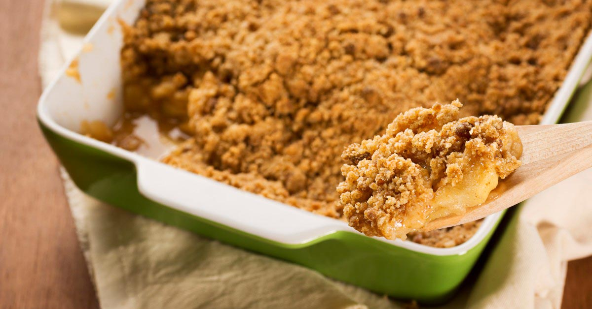Scooping a serving of Apple Betty out of a baking dish with a wood spoon.